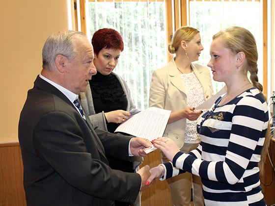 Василий Станкевич вручает удостоверение члена молодежной палаты учащейся Вымнянской ДССШ Ирине Синяковой