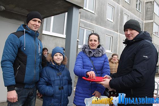 На снимке: руководитель проекта ГП «УКС города Витебска»   Сергей Шнипов (справа) вручает ключи от квартиры семье Бредихиных.