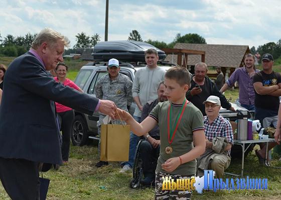 На снимке: Юрий Осипов вручает сладкие призы юным участникам соревнований.