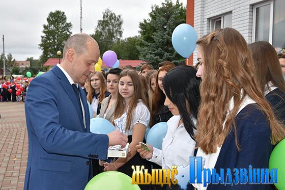Алексей Ларькин вручает десятиклассникам отличительные значки